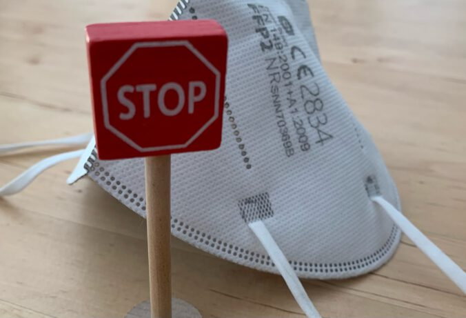 Stop-Schild vor Corona-Maske